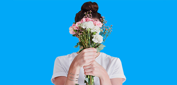 A person hiding behind flowers.